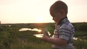 Un petit garçon mignon regarde avec l'intérêt des des billets de banque cent dollars, mouvement lent clips vidéos