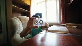 Un petit garçon a mis un stylo par la cassette et les débuts écrivant quelque chose dans la note clips vidéos