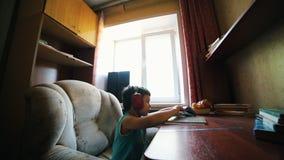 Un petit garçon a mis une cassette dans la plaque tournante et écoute la musique dans les écouteurs banque de vidéos
