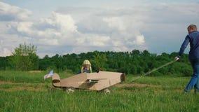 Un petit garçon monte un avion fait maison de carton Concept de famille amicale clips vidéos