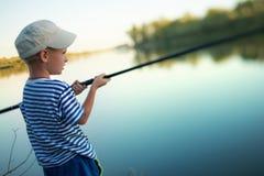 Un petit garçon pêche des articles de pêche en rivière Photos libres de droits