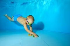 Un petit garçon plonge sous l'eau au fond dans la piscine du ` s d'enfants et rassemble des jouets du fond Photographie sous-mari images stock