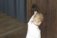 Un petit garçon près de la porte en bois image stock