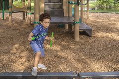 Un petit garçon quitte le terrain de jeu avec sa baguette magique de savon de bulle photos libres de droits