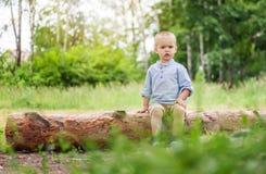 Un petit garçon sérieux 2 années repose sur un identifiez-vous une forêt d'été photos stock