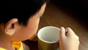 Un petit garçon s'asseyant à la table en bois par la fenêtre à la maison pour boire une tasse de chocolat chaud il tiennent la ta banque de vidéos
