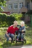 Un petit garçon s'asseyant dans un fauteuil roulant et marchant avec sa mère Image libre de droits