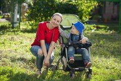 Un petit garçon s'asseyant dans un fauteuil roulant et marchant avec sa mère Images libres de droits
