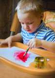 Un petit garçon s'assied à la table d'enfants, tenant une brosse, peinture, peintures Images stock