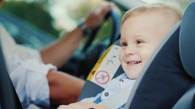 Un petit garçon s'assied dans un siège de voiture près de son père, souriant heureusement Concept - sécurité et soin Images libres de droits