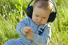 Un petit garçon s'assied sur un pré avec des écouteurs Image libre de droits