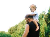 Un petit garçon s'est élevé sur son épaule du ` s de père photographie stock