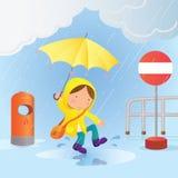 Un petit garçon saute dans un magma d'eau de pluie pour faire l'amusement Image stock