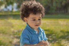 Un petit garçon seul marche avec une expression intéressée regardant vers le bas photo libre de droits