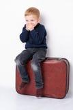 Un petit garçon silling sur un tronc Photo stock