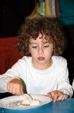 Un petit garçon a son désert photos stock