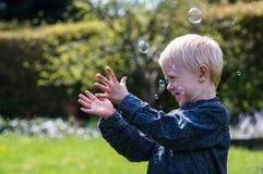Un petit garçon souffle des bulles de savon dans le jardin un jour d'été image libre de droits
