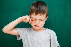 Un petit garçon sur un fond vert essuie ses larmes avec ses mains photo stock