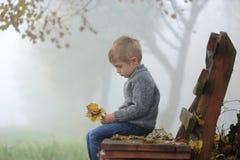 Un petit garçon triste s'assied sur un banc avec sa tête vers le bas photo stock