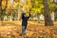 Un petit garçon utilisant des jeans et une veste bleue jette joyeux le YE photos stock