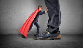 Un petit homme d'affaires dans un cap de super héros essayant d'éloigner les jambes géantes d'homme Photographie stock