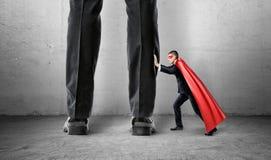 Un petit homme d'affaires dans un cap de surhomme essayant d'éloigner les jambes géantes d'homme Images stock