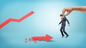 Un petit homme d'affaires est soulevé par une main humaine géante sur un fond bleu au-dessus d'une flèche cassée rouge de statist Photos stock