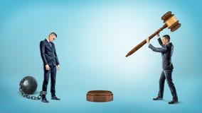 Un petit homme d'affaires frappe un marteau sur un bloc sain près d'un homme d'affaires enchaîné par cheville triste images libres de droits