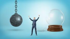 Un petit homme d'affaires victorieux se tient près d'une sphère en verre cassée et d'un fer détruisant la boule Photo libre de droits