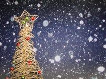 Un petit jouet d'arbre de Noël de couleur d'or avec les boules vertes et rouges sur un fond bleu avec une texture de neige image stock
