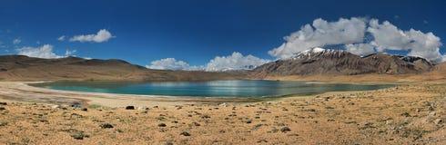 Un petit lac de montagne au milieu d'un désert en pierre, à l'arrière-plan les chaînes de montagne, dans un ciel bleu lumineux, n Photos libres de droits