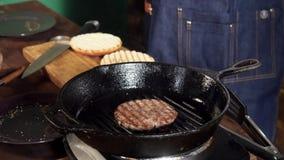 Un petit pâté d'hamburger faisant frire sur un gril de fonte Longueur courante L'hamburger Patty est préparé sur la casserole de  clips vidéos