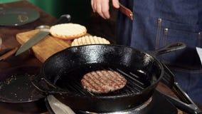 Un petit pâté d'hamburger faisant frire sur un gril de fonte Longueur courante Le petit pâté d'hamburger est préparé sur la casse clips vidéos