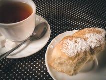 Un petit pain et une tasse de thé Photos stock