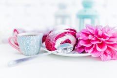 Un petit pain rouge de gâteau de velours découpé en tranches avec la tasse de café ou thé et fleurs Photographie stock