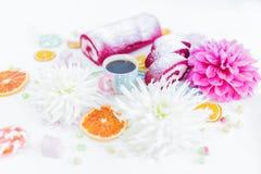 Un petit pain rouge de gâteau de velours découpé en tranches avec la tasse de café ou thé, fleurs et oranges sèches Photo stock