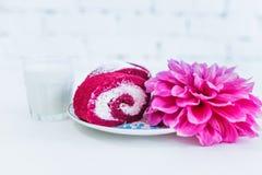 Un petit pain rouge de gâteau de velours découpé en tranches avec la tasse de lait et de fleurs Photos libres de droits