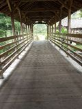 un petit pont en bois avec un toit carrelé pour traverser une petite rivière photo libre de droits