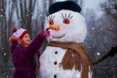 Un petit regard gai de fille au visage drôle de bonhomme de neige Photographie stock