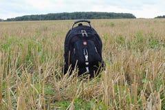 Un petit sac à dos de touristes se tient au sol au milieu d'un champ d'inclinaison photo libre de droits
