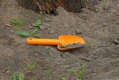 Un petit scoop en plastique jaune de bébé se trouve sur le sable gris photographie stock