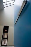 Un petit signe de sortie hors d'une grande salle bleue Photos libres de droits