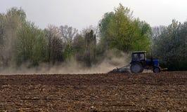 Un petit tracteur cultive un champ labouré dans la traînée de la poussière de forêt derrière le tracteur images stock