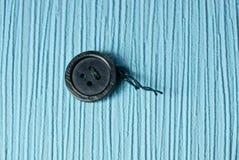 Un petit vieux bouton noir avec un fil sur la table Image stock
