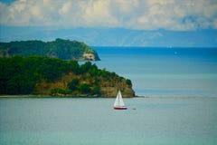 Un petit yacht dans un vaste oc?an ; paysage marin tranquille avec l'eau tranquille et des ?les loin Effet de peinture ? l'huile photo stock