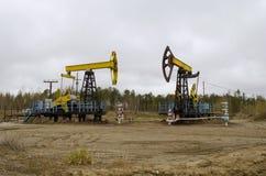 Un petróleo pozo con un bombeo de balanceo de la barra Fotografía de archivo libre de regalías