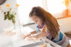 Un peu de cuisinier La fille dans sa cuisine prépare les biscuits faits maison et les met sur les étagères Image stock