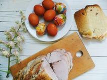 un pezzo di carne arrostita, di uova, di fiori di Pasqua e di castagna su una tavola bianca Immagine Stock