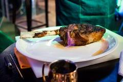 Un pezzo di carne fritta su un osso con le lingue della fiamma Immagine Stock