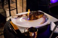 Un pezzo di carne fritta su un osso con le lingue della fiamma Fotografie Stock Libere da Diritti